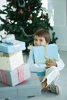 Boy sitting next to stack of Christmas presents, holding one against chest