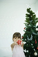 Girl holding out star decoration in front of Christmas tree