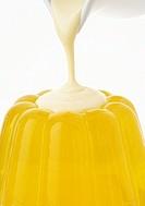Pouring custard over lemon jelly