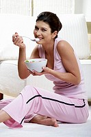 Woman eating yoghurt with kiwi fruit and strawberries