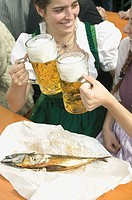 Two women clinking litres of beer at Oktoberfest