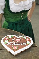 Lebkuchen heart on rustic table, woman in background