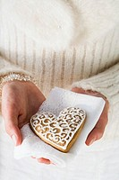 Hands holding gingerbread heart on napkin Christmassy
