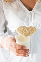 Hand holding a glass of milk with a biscuit