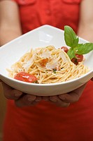 Hands holding plate of spaghetti with Parmesan and basil