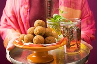 Woman holding tray of falafel chick-pea balls and tea
