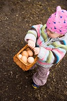 Small girl holding basket of brown eggs