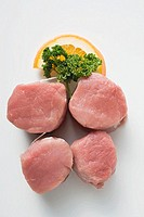 Four pork medallions, garnished with parsley and orange