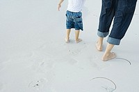 Father and child walking on beach