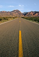 A long stretch of blacktop reaches for the Chisos Mountains on the horizon in Big Bend National Park, Texas, USA
