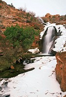 Snow and ice surrounds Faux Falls on a cold winter day, Moab, Utah, USA