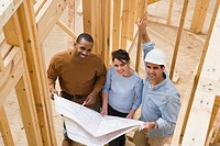 Couple and contractor with blueprints standing in framework