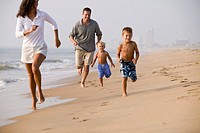 Parents running along beach with sons