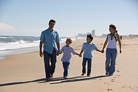 Parents and sons walking hand in hand along beach