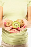Young woman holding three kiwis, mid section focus on kiwis