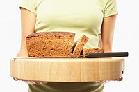 Young woman holding loaf of bread on cutting board, mid section