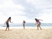 Three young people playing volleyball at beach