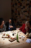 Four adults drinking sake at table in sushi bar, laughing