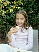 Girl 5-7 sitting at table in garden holding bread, smiling, portrait