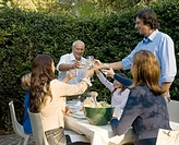 Three generation family toasting drinks at garden table, smiling