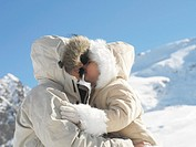 Mother and daughter 3-6 embracing on mountain slope, close-up