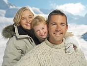 Parents and daughter 3-6 in snowscape, smiling, portrait