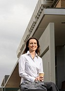 Businesswoman holding disposable cup outdoors, smiling