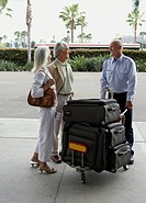 Airport porter helping senior couple with luggage at airport