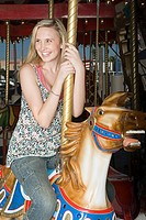 Teenage girl riding carousel