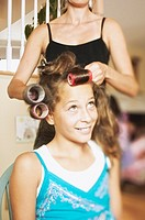 Pre-teen girl getting rollers put into hair