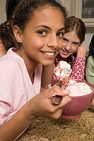 Preteen girls eating ice cream sundaes