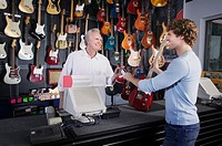 Man buying electric guitar in music store