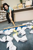Woman sweeping crumpled paper