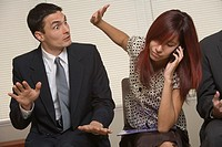 Woman on cell phone ignoring annoyed businessman