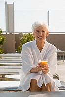 Woman in bathrobe sitting with glass of orange juice