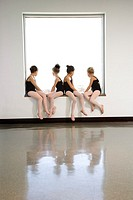 Rear view of ballet students sitting in window
