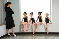 Ballet instructor addressing students sitting in window