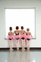 Rear view of ballet students standing by window and embracing
