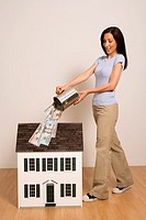 Woman pouring money on miniature house