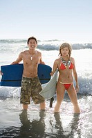Couple in ocean with surfboards