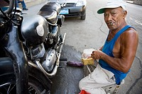 Man smoking cigar and repairing his motorbike. Havana, Cuba
