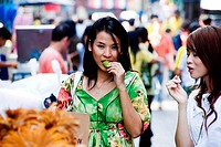 Two young women standing in a market and eating