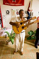 Musician livening up the working day in a sewing workshop. Baracoa. Guant&#225;namo province. Cuba
