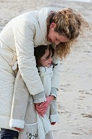 Mid adult woman hugging her daughter on the beach