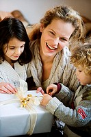 Mid adult woman with her son and daughter opening a Christmas present