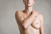 naked young woman covering one of her breasts