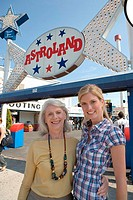 Senior woman and a young woman standing in front of an amusement park, Coney Island, New York City, New York, USA