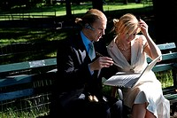 Businessman and businesswoman sitting on a park bench looking at a laptop