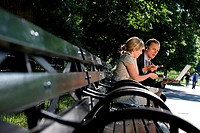 Businessman and businesswoman sitting on a park bench and looking at a laptop