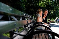 Businessman holding a laptop with a businesswoman sitting on a park bench and smiling